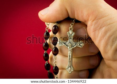 An hand is holding a crucifix - stock photo