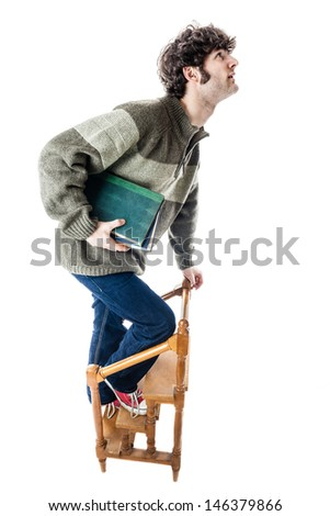 an handsome guy, maybe a student, in casual clothing clambering on a small wooden library ladder. isolated on white