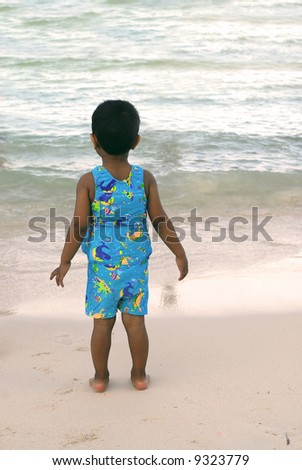 an handsome Indian boy looking at the beach - stock photo