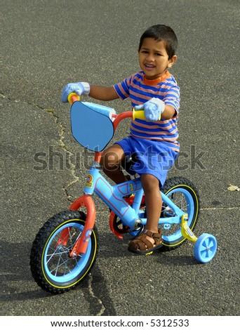An handsome Indian kid enjoying his bike - stock photo