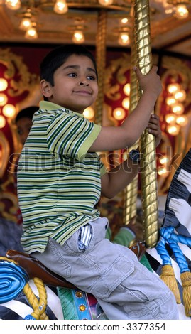 An handsome indian kid having fun at a local carnival - stock photo