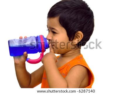 An handsome indian kid having fun drinking juice - stock photo