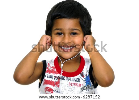 An handsome indian kid having fun listening to music - stock photo