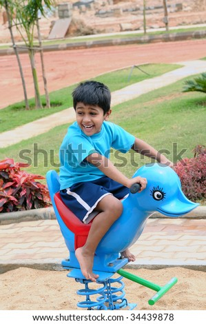 An handsome Indian kid having funat a local park - stock photo