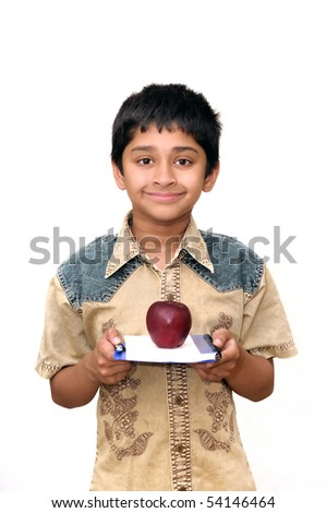 An handsome Indian kid holding apple and a book - stock photo