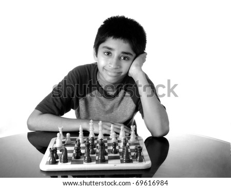 An handsome indian kid playing the game of chess - stock photo