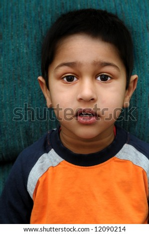 An handsome Indian kid sitting very anxious - stock photo