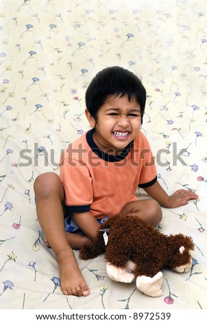 An handsome kid playing with a stuffed toy - stock photo