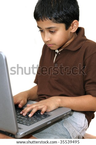 An handsome young Indian kid working with a laptop