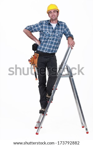 An handyman on a ladder. - stock photo
