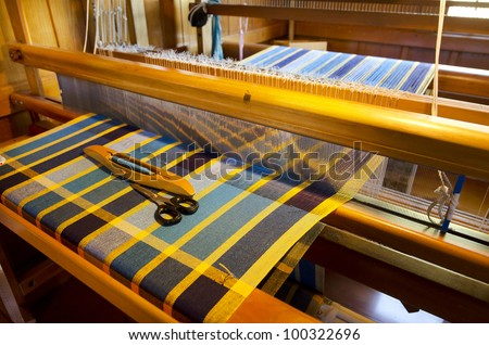 An homemade loom white threads and sawing tools. - stock photo