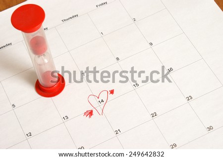 An hourglass and reminder on a calendar for the upcoming Valentines Day. - stock photo