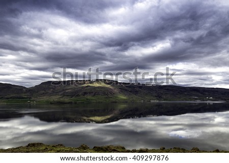 An Icelandic fjord in really calm weather, mountains reflected in the mirror like surface of the sea - stock photo