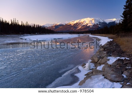 An icy river in the mountains during winter.