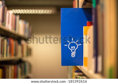 an idea icon on book in a bookshelf - stock photo