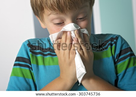 An ill boy with flu blowing nose at home - stock photo