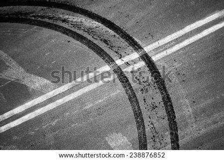 An illegal maneuver concept. Crossing of double dividing lines road marking and tires track - stock photo