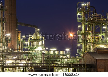 An illuminated chemical plant at night - stock photo