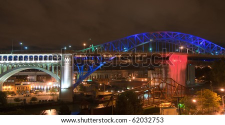 An illuminated man-made waterfall pours from the deck of bridge in Cleveland Ohio - stock photo