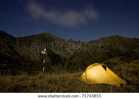 An illuminated tent at night next to a pole with arrows in a wild mountain scenery and the sky full of stars - stock photo