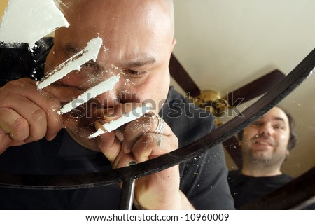 An image about drug abuse.  Male snorting lines of cocaine on a dirty glass table while another waits his turn.  View from underneath and through the glass.