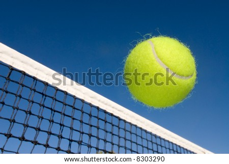 An image depicting the concept of tennis, including a ball gliding over the net. - stock photo