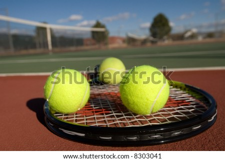 An image depicting the concept of tennis, including the court, racquets, balls and blue outdoors. - stock photo