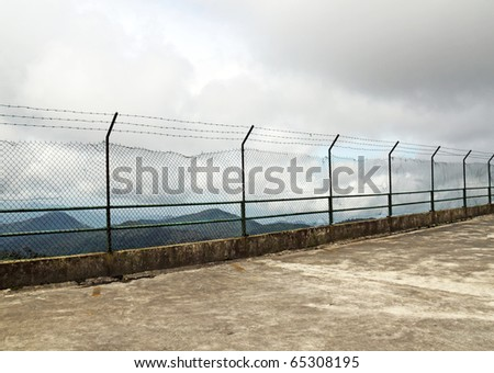 An image of a barbed wire high security fence on the ledge of a cliff with a view of a mountainous range. - stock photo