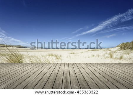 An image of a beach and a wooden jetty in the foreground - stock photo