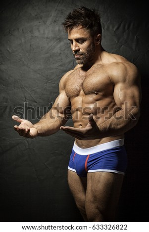 An image of a bearded muscular man watching his hands