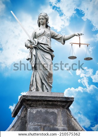An image of a beautiful justitia statue in front of a blue sky - stock photo
