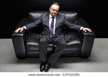 An image of a businessman resting on a soft black sofa