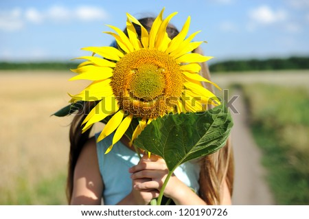 An image of a girl hiding behind a smiling sunflower - stock photo