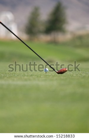 An image of a golf club and ball on tee - stock photo
