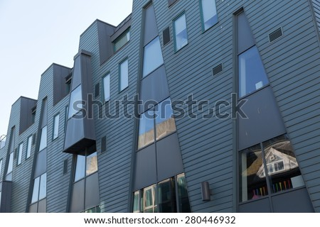 An image of a grey metal cladded facade with angled lines dividing the material of the facade - stock photo