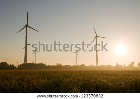 An image of a group of windmills in the field - stock photo