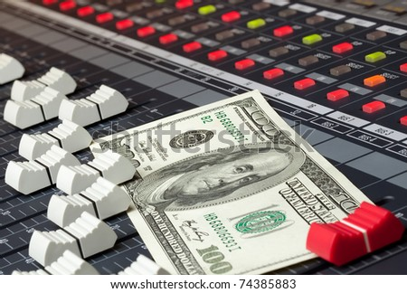 An image of a hundred dollar bill sitting on a mixing board. - stock photo