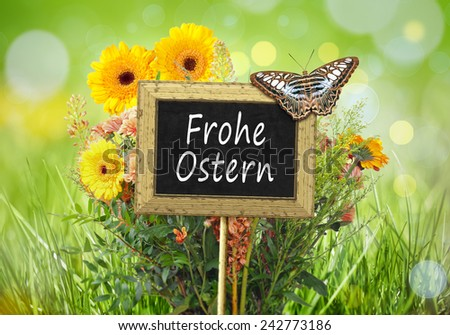 An image of a little chalkboard in the garden with the text Happy Easter in german language - stock photo