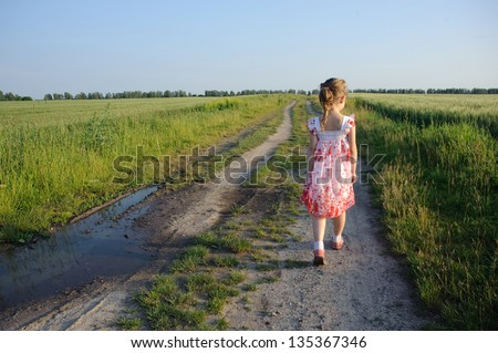An image of a little girl walking on the road - stock photo