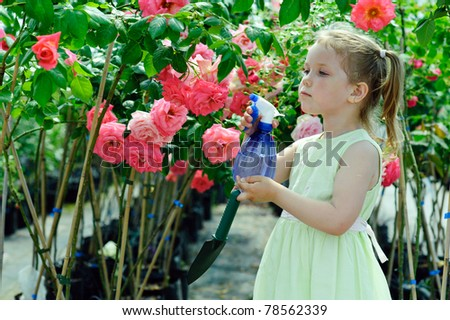 An image of a little girl watering flowers in a greenhouse - stock photo