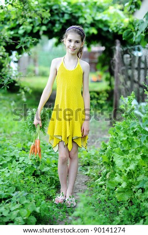 An image of a little girl with fresh orange carrots
