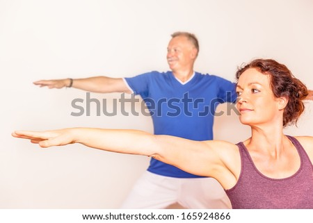 An image of a man and a woman doing yoga exercises - stock photo