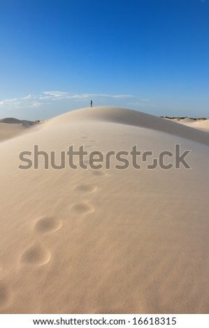 An image of a man's path of footprints leading into the distance - stock photo