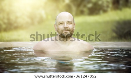 An image of a middle age man relaxing at the pool - stock photo