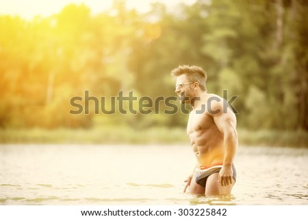 An image of a muscular man in the lake