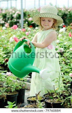 An image of a nice little girl watering flowers - stock photo
