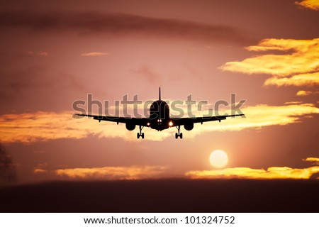 An image of a plane in the sunset sky - stock photo