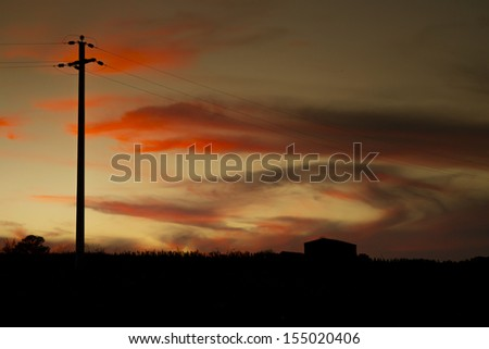 An image of a power cable in the evening sunset sky - stock photo