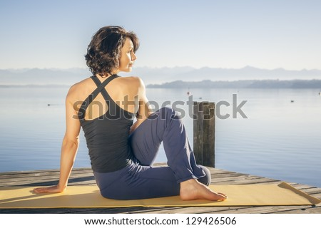 An image of a pretty woman doing yoga at the lake - Ardha Matsyendrasana - stock photo