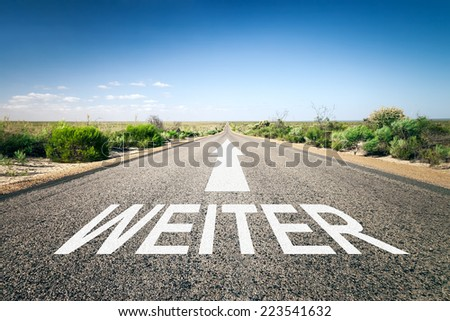 An image of a road to the horizon with text next in german language - stock photo